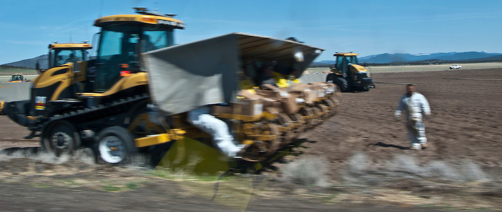 farm workers ride a machine to plant crops blurry image due to motion blur from moving automobile on the highway