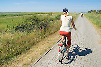 Female riding bicyle on carless Island of Juist, Germany