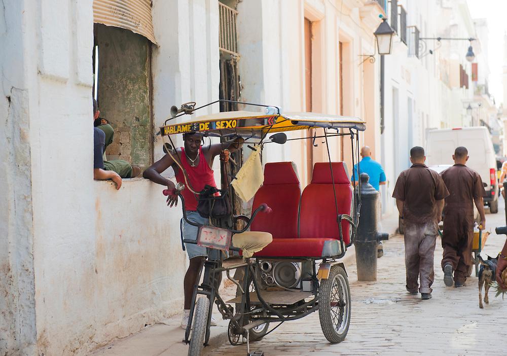 Havana, Cuba - October 2015: A bike taxi driver waits clients in the street of Havana.