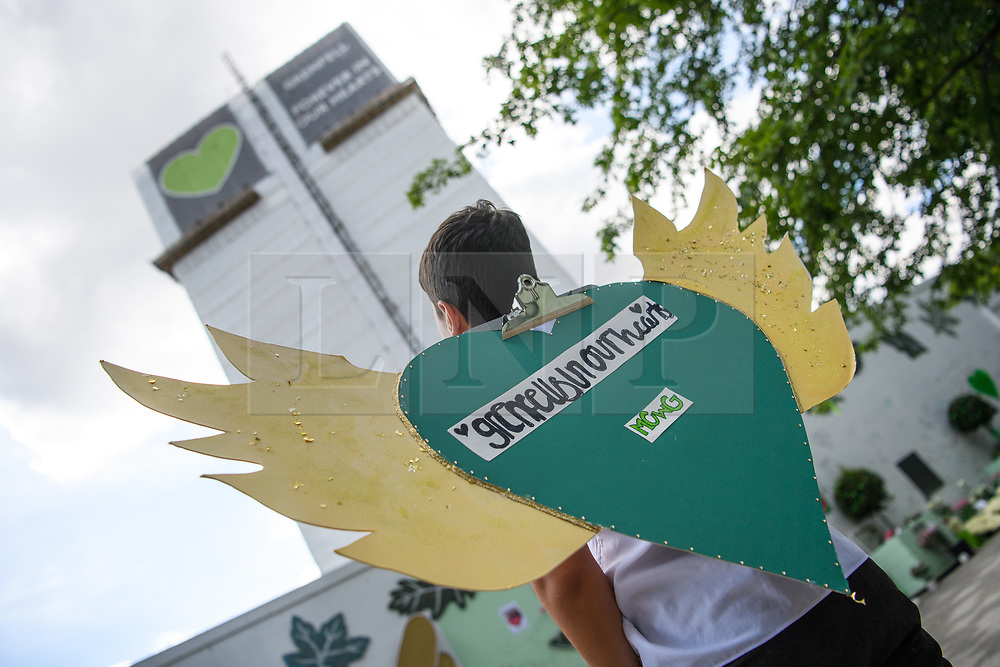 © Licensed to London News Pictures. 14/06/2021. London, UK. Mo-k (Mohammed Choaibi), 11 and three quarters, poses with his hand made sign commemorating victims on the fourth anniversary of the Grenfell Tower fire that claimed 72 lives in 2017 [permission to publish granted by father Rashid Choaibi]. Photo credit: Guilhem Baker/LNP