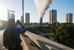 © Licensed to London News Pictures. 14/06/2017. London, UK. Photo credit: A young man takes a photo with his mobile phone of a major fire that has engulfed the 27-storey Grenfell Tower block in Latimer Road, White City. The blaze started early Wednesday morning and has spread through most of the building. Ray Tang/LNP