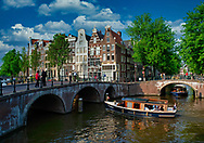 Boats stream down the Kelzersgracht Canal in Amsterdam.