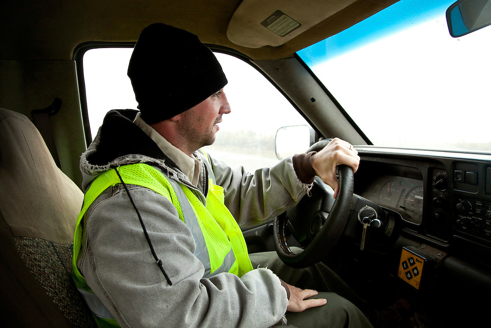 Landfill worker in truck cab driving wearing yellow safety vest