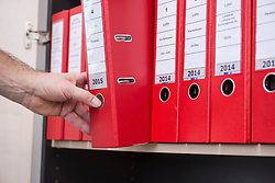 Man taking confidential file from filing cabinet, Munich, Bavaria, Germany