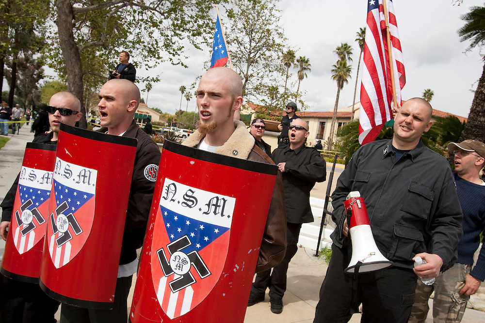 Members of the National Socialist Movement, a Neo Nazi group, led by Southwestern Regional Director Jeff Russell Hall, right, with megaphone, rallies in Claremont, California against illegal immigration. Please contact Todd Bigelow directly with your licensing requests.