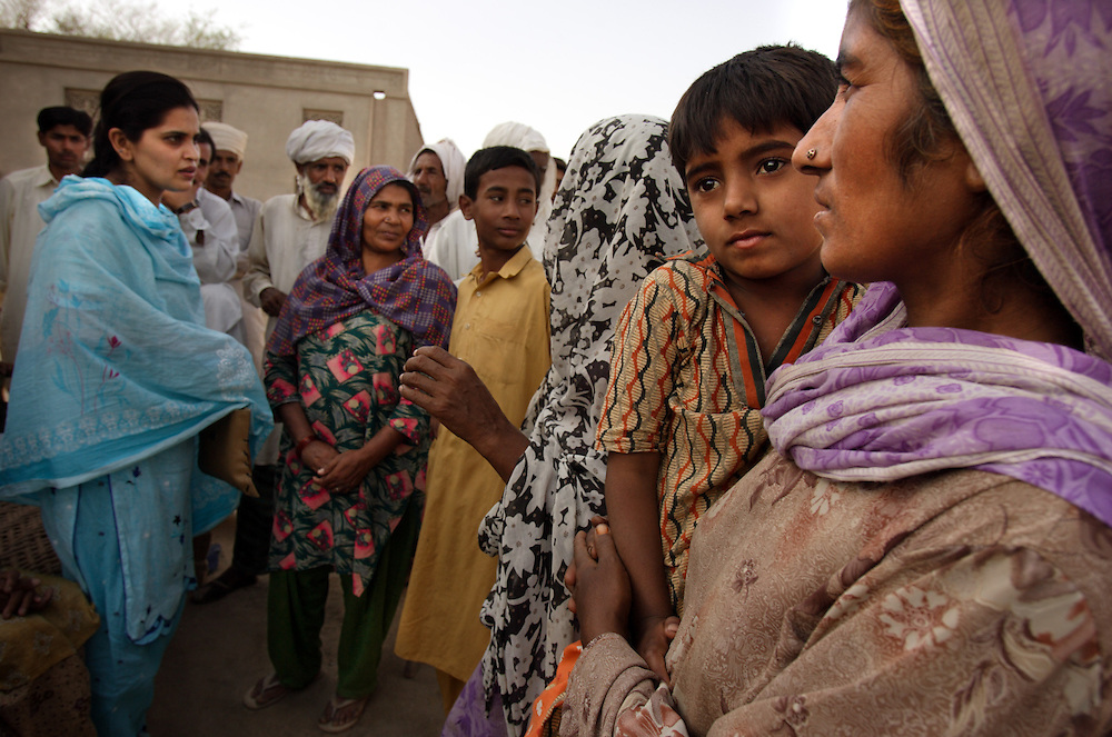 "Tasleem, holds daughter Rafiabibi, 6, as social worker Asia Perveen, in blue, talks to relatives, Dera, Pakistan, April 26, 2005. Perveen speaks about Tasleem and her sister Zubada's  potential case against the neighbors who gang raped them when they felt they were dishonored by Zubada's son Naeem. Members of the Human Rights Commission in Multan, including Perveen, are working with the women to get them legal representation so they can fight the accusers in court. ""I want them to be punished,"" said Tasleem. ""They are our enemies, I will be afraid until they are hanged publicly."""