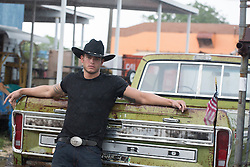 handsome All American cowboy in a black tee shirt, jeans and cowboy hat near an old pick up truck