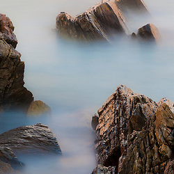 Blurred waves around the rocks at Wallis Sands State Park in Rye, New Hampshire.