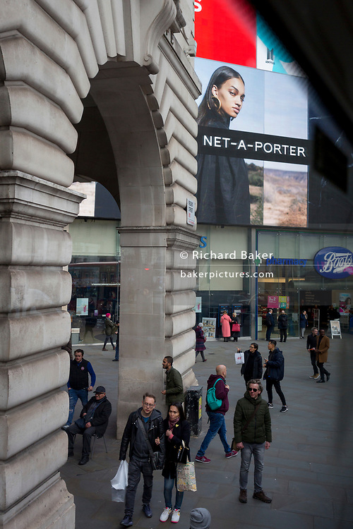 A model in an ad for clothing brand Net-a-Porter, looks down on passers-by, in Piccadilly Circus, on 7th March 2019, in London, England.