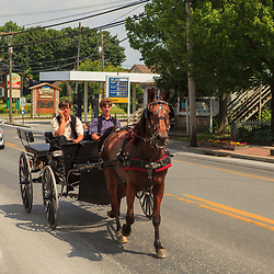 Intercourse, PA, USA - June 17, 2012: Two young Amish men ride in an open horse-drawn wagon in Intercourse, PA.
