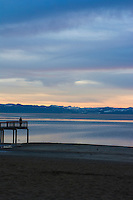Adult stands on pier at sunset on Kings Beach, Lake Tahoe, California.
