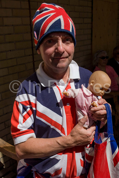 Royalist portrait with toy doll as tension mounts outside St Mary's Hospital, Paddington London, where media and royalists await news of Kate, Duchess of Cambridge's impending labour and birth. Some have been camping out for up to two weeks during a UK heatwave, having bagged the best locations where an heir to the British throne will eventually be shown to the world.