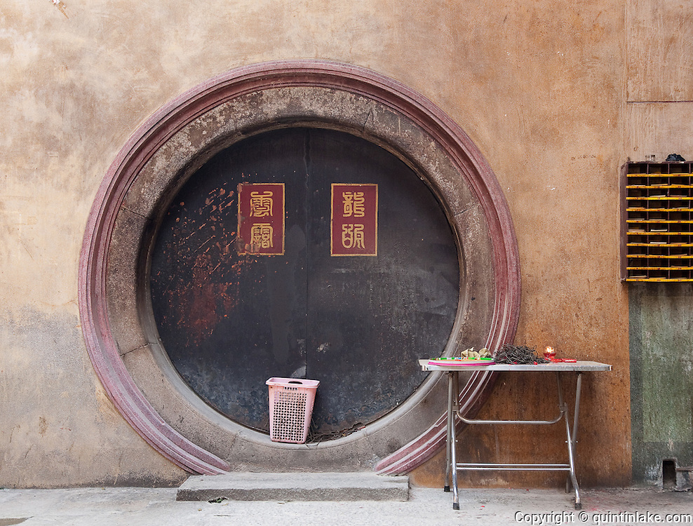 Round Door and table laid with spiral incense hooks,  Nghia An Hoi Quan Pagoda on 678 Nguyen Trai Street in Cholon, Ho Chi Minh City