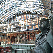 A statue of former Poet Laureate Sir John Betjeman by British sculptor Martin Jennings under the distinctive iron and glass arched cover over the platforms of St Pancras Railway Station (now known as St Pancras International). The renovated station features distinctive Victorian architecture and serves as a Eurostar terminal for high-speed trains to Europe. There are also platforms for domestic train services. The distinctive train shed roof was designed by William Henry Barlow.