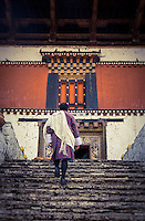PARO, BHUTAN - CIRCA October 2014: Bhutamese man walking into the Paro Rinpung Dzong in Bhutan
