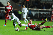 Swansea city's Nathan Dyer is tackled by Boro's Nicky Bailey. Capital one cup, quarter final, Swansea city v Middlesbrough at the Liberty Stadium in Swansea, South Wales on Wednesday 12th Dec 2012. pic by Andrew Orchard, Andrew Orchard sports photography,