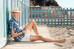 Boy beach summer holiday straw hat sitting