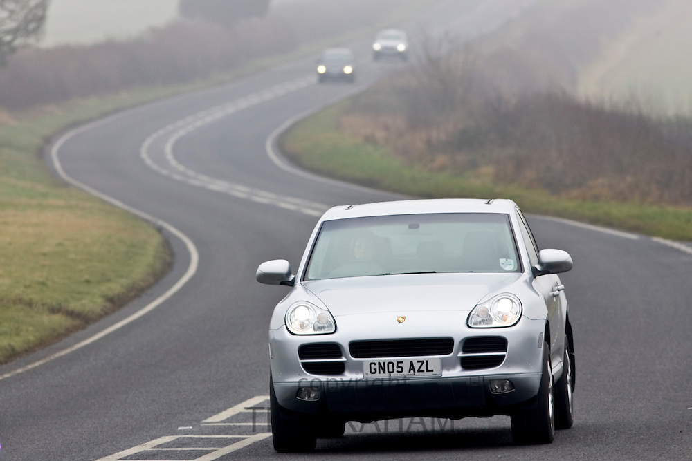 Porche Cayenne 4-wheel drive car drives along foggy road, Oxfordshire,  United Kingdom