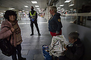 A security guard at the central Barcelona train station warns a group of homeless women that they cannot be at the train station during the day. During the period of confinement decreed by spanish Government due to COVID19 crisis, homeless people cannot be in squares, libraries, or bars as before. Barcelona, March 24th. Photo by Eva Parey.<br /> <br /> Many homeless have been living in Barcelona for a while, sleeping on its streets, there are around 2,500 people, of different nationalities, ages and genders, but it is the quiet of the city - with hardly any passers-by -, in State of Alarm, that betrays their presence on the streets.<br /> The confinement order issued on March 15 cannot be applied to them. Their problem is twofold. Find a place to spend the day and avoid to be exposed to COVID disease19. Some have been able to occupy spaces in the city that before, being visible for the society, were prohibited. Others would like to occupy any of the places in the social shelters that the Barcelona City Council has specifically opened for them. More than fear of the disease, there are other fears. Loss of freedom seems the most precious asset for those who do not want to confine themselves in a closed space, in addition to protecting themselves from possible thefts or conflicts of all kinds. Behind each face there is a story. Some have been with this way of life for some time, but others, the cessation of many jobs or the closing of borders, have left them trapped in the street with no other option.