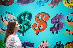 """© Licensed to London News Pictures. 08/06/2015. London, UK. A Sotheby's staff member looks at """"Dollar Signs"""" by Andy Warhol (est. £4.5 - £6.5m), at the preview of """"To the Bearer on Demand"""", a private collection of 21 works inspired by the US dollar, including Andy Warhol masterpieces, which will be auctioned on 1 and 2 July.  The collection is estimated to realise £50 million. Photo credit : Stephen Chung/LNP"""