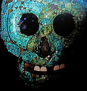 Turquoise mosaic mask AD 1400-1521.  A pair of serpents is entwined around the eyes, nose and mouth of this mask.  Two serpent tails meet at the top and a feathered plume hangs down on either side.  Snakes were used metaphorically to represent the attributes of two well-known Aztec deities : The Rain God Tlaloe and the Creator God Quetzalcoatl.