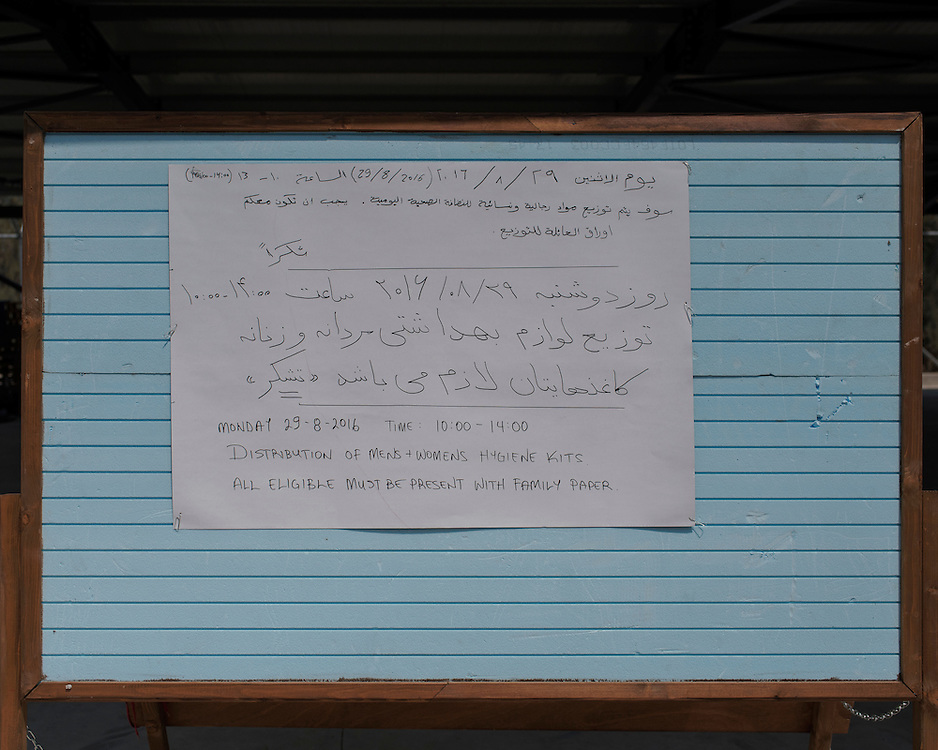 The noticeboard in the  First Reception Centre (Hot-Spot) of Leros, Greece, advertising, in Arabic and English, the distribution of hygiene kits. <br /> <br /> The Hot Spot in Lepida opened on the 26th of February 2016 in the grounds of the former Lepida psychiatric hospital.  At the beginning it served as a registration camp for refugees and migrants who were travelling to Europe through Greece but since the closure of the borders in March 2016 it serves as a permanent camp. People are allowed to go out, they have three meals a day, the prefabricated huts have a bathroom and are air-conditioned and compering to other refugee camps in Greece the conditions are bearable.