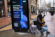 HM Government, and NHS advertising boards advise regular hand washing to help prevent Coronavirus contamination on 14th March 2020 in Birmingham, England, United Kingdom. Due to the rapidly spreading coronavirus outbreak a number of mainly Chinese / Asian people are wearing face masks in public. Coronavirus or Covid-19 is a new respiratory illness that has not previously been seen in humans. While much or Europe has been placed into lockdown, the UK government is due to announce more stringent rules as part of their long term strategy.