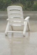 outdoor garden chair on roof terrace on a rainy day seen through a window with rain droplets