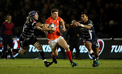 Saracens Owen Farrell sprints past Sale Sharks Magnus Lund(left) and Sale Sharks Denny Solomona (right) during the European Champions Cup, pool three mach at the AJ Bell Stadium, Salford.