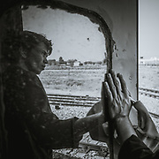 I was travelling on the Shatabdi Express from New Delhi to Jaipur. I went to the end of the train where I saw this guy, who was the janitor of the train, opened the door and stood there for a while. I really liked his posture, how he was looking somewhere far away with hope in his eyes, reflected back on the glass. I had the camera on me, I just quickly took a few picture of him.
