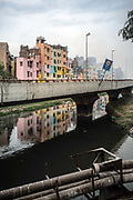 Gaily painted apartment blocks overlook a grim flyover and a polluted drain open sewer in Nizamuddin, New Delhi, India