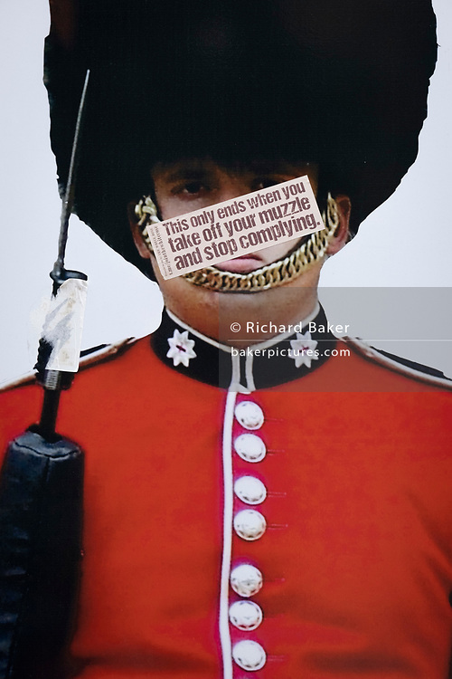 The image of a guardsman's face has been obscured by an anti-vaxx message mocking pandemic face coverings, on Covid 'Freedom Day'. This date is what Prime Minister Boris Johnson's UK government has set as the end of strict Covid pandemic social distancing conditions with the end of mandatory face coverings in shops and public transport, on 19th July 2021, in London, England.