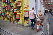 Alphabet street art covering a yellow wall with letter forms in Spitalfields, London, UK. Street art in the East End of London is an ever changing visual enigma, as the artworks constantly change, as councils clean some walls or new works go up in place of others. While some consider this vandalism or graffiti, these artworks are very popular among local people and visitors alike, as a sense of poignancy remains in the work, many of which have subtle messages.