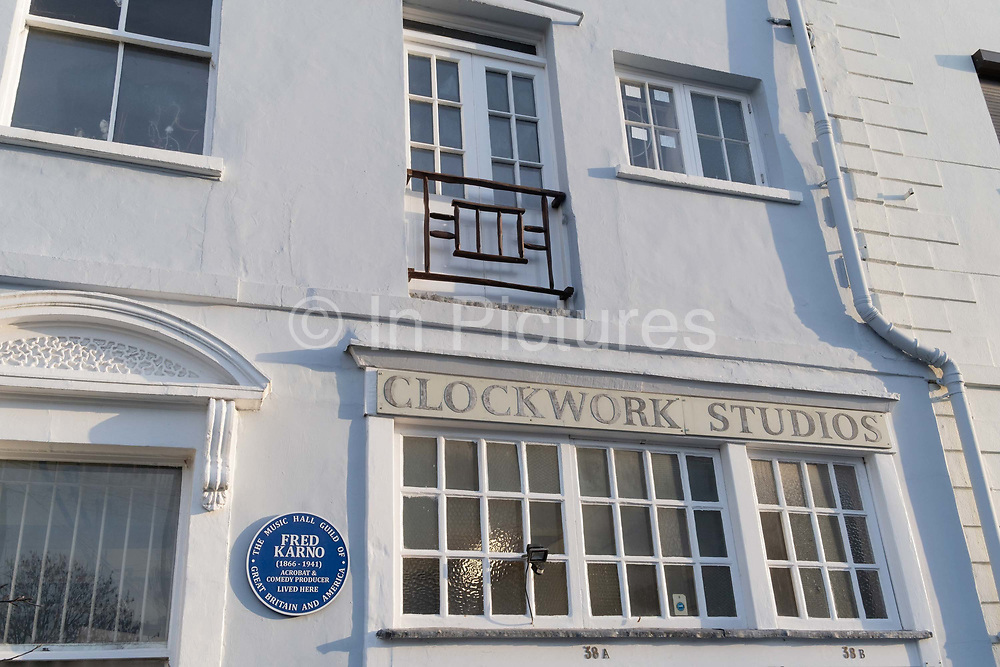 """An exterior of Clockwork Studios on Southwell Rd, in Brixton, south London, on 11th February 2021, in London, England. Clockwork Studios currently houses over 20 diverse independent art businesses but once accomodated comedians and clock makers. At the turn of the 20th century the """"Fun Factory"""", as it was then known, was home to Fred Karno's Vaudeville theatre group. Silent movie stars Charlie Chaplin and Stan Laurel, two of Karno's most notable performers would have spent many hours there rehearsing. The Music Hall Guild of Great Britain and America recently fixed a commemorative blue plaque next to the main door to remember the comedy impresario Fred Karno. Also, while still young, future British Prime Minister, John Major lived a few streets away."""