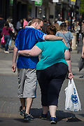 A slim man and obese woman walk through Windsor, on 14th May 2018, in London, England.