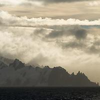 Clouds engulf mountains on the Antarctic Peninsula, Antarctica.