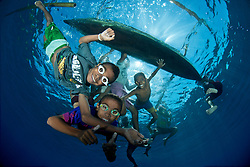Local kids eagerly pose for a photo beneath their dugout canoe. Jan Village, Pulau Pura, Alor, Indonesia, Indian Ocean