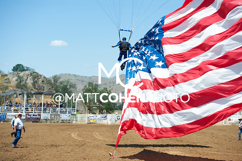 Kent Lane parachutes in with the flag at the Woodlake Lions Rodeo.<br /> <br /> <br /> UNEDITED LOW-RES PREVIEW<br /> <br /> <br /> File shown may be an unedited low resolution version used as a proof only. All prints are 100% guaranteed for quality. Sizes 8x10+ come with a version for personal social media. I am currently not selling downloads for commercial/brand use.