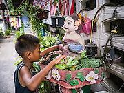 """29 MARCH 2013 - BANGKOK, THAILAND: Boss, the nine year old son of Saiyuud Diwong """"Poo""""  plays at a small fountain in front of Poo's home in Klong Toey. PHOTO BY JACK KURTZ"""