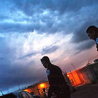 072413  Adron Gardner/Independent<br /> <br /> Gallup Police Officer rookie Charles Wommack, left, heads out for a night shift partner Officer Steven Peshlakai under stormy skies in Gallup Wednesday.