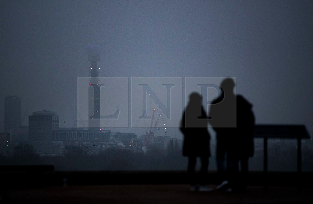 © Licensed to London News Pictures. 22/01/2020. London, UK. Visitors to Primerose Hill look out at BT Tower and the London Eye swathed in cloud, as the sub zero temperatures come to an end. Photo credit: Peter Macdiarmid/LNP
