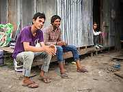 04 SEPTEMBER 2013 - BANGKOK, THAILAND:  Cambodians who are construction workers relax near their dorms at the construction site of a new high rise apartment / condominium building on Soi 22 Sukhumvit Rd in Bangkok. Most of the workers at the site are Cambodian immigrants.    PHOTO BY JACK KURTZ