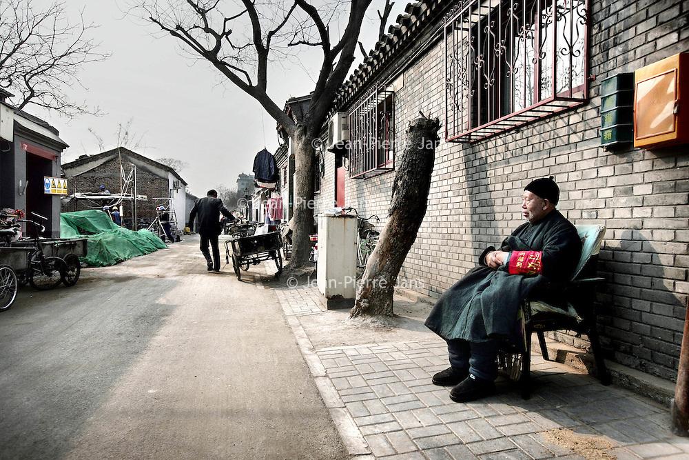 China,Beijing ,13 maart 2008..Wijkoudere voor zijn huis in een gerenoveerde Huton (oud buurtje) in de oude stadswijk van Beijing..Dit is 1 van de weinig overgebleven Hutons van Beijing. De meeste oude wijkjes zijn met de grond gelijk gemaakt en hebben plaats gemaakt voor grote hogenieuwe kantoorgebouwen en flats..Met het vooruitzicht op de Olympische Spelen in augustus van dit jaar zijn enkele overgebleven Hutons gerenoveerd speciaal voor de toeristen.