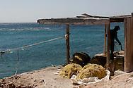 Greece, Koufonissi, Cyclades: A fisherman adjust a fishing nets