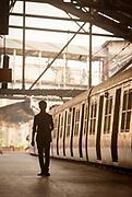 Silhouette of man standing on train station, Mumbai, India