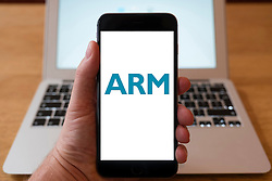 Using iPhone smartphone to display logo of ARM, microprocessor designer