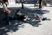 Al liggend fotografeert een man twee op de grond liggende kinderen op het Domplein