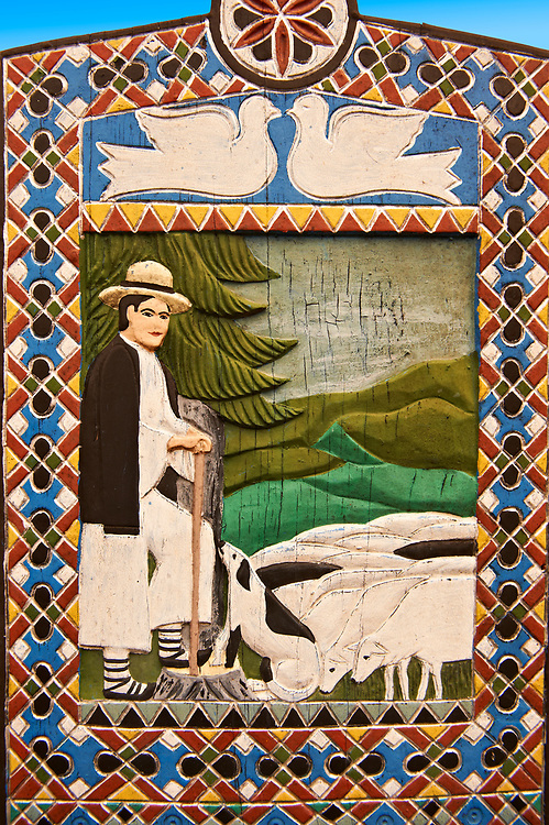 Tombstone of a shepherd in the fields,  The  Merry Cemetery ( Cimitirul Vesel ),  Săpânţa, Maramares, Northern Transylvania, Romania.  The naive folk art style of the tombstones created by woodcarver  Stan Ioan Pătraş (1909 - 1977) who created in his lifetime over 700 colourfully painted wooden tombstones with small relief portrait carvings of the deceased or with scenes depicting them at work or play or surprisingly showing the violent accident that killed them. Each tombstone has an inscription about the person, sometimes a light hearted  limerick in Romanian. .<br /> <br /> Visit our ROMANIA HISTORIC PLACXES PHOTO COLLECTIONS for more photos to download or buy as wall art prints https://funkystock.photoshelter.com/gallery-collection/Pictures-Images-of-Romania-Photos-of-Romanian-Historic-Landmark-Sites/C00001TITiQwAdS8