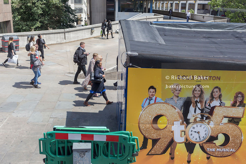 Commuters walk over London Bridge passing a billboard for the musical 'Nine to Five' presented by its original star Dolly Parton, on 17th June 2019, in London, England.