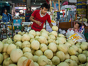 03 APRIL 2015 - CHIANG MAI, CHIANG MAI, THAILAND:  A vendor stacks melons in the market in Chiang Mai, Thailand.      PHOTO BY JACK KURTZ